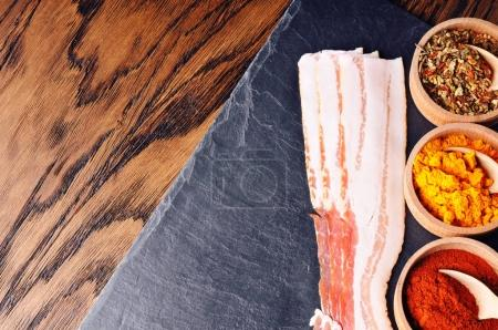 Raw bacon slices and wooden spoons in bowls with different dry spices on slate slab