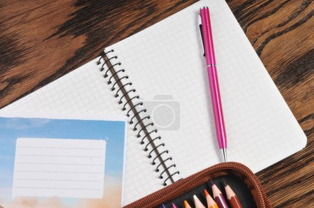 Pencil case full of color pencils with notebook, school copybook and pen on the brown wooden table