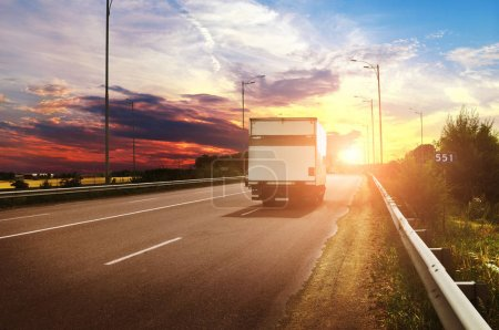 White box truck on countryside road against night sky with beautiful sunset