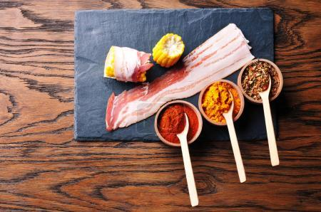 Raw bacon slices with yellow sliced corn cobs and wooden bowls with dry spices and spoons on the dark blue board on the brown wooden background