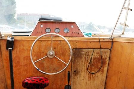 Wooden control panel with metal steering wheel on the captain bridge of the old motor boat