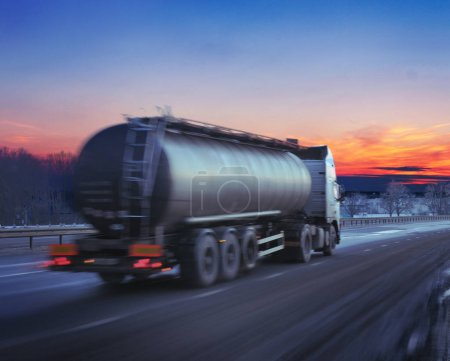 Truck with fuel on winter highway at sunset