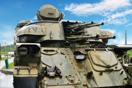 Old soviet green anti-aircraft vehicle ZSU-23-4 against blue sky with white clouds