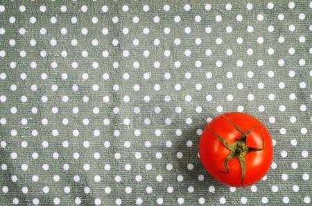 One red ripe tomato on the dotted grey napkin background