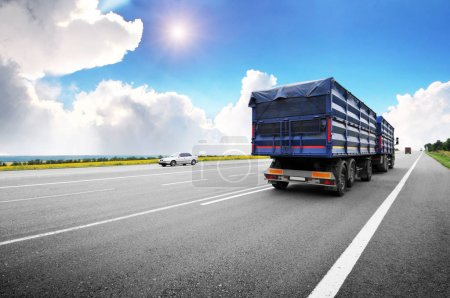 Rear view of the big truck with blue trailer on the countryside road against blue sky with clouds and sun