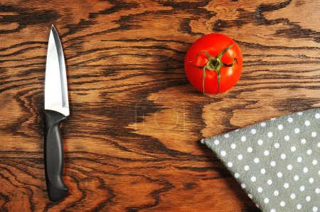 Top view of red ripe tomato, black knife with dotted napkin on the wooden background