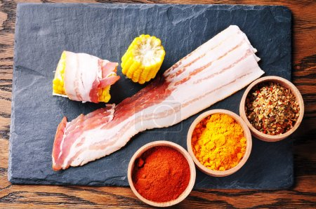 Raw bacon slices and wooden bowls with dry spices the dark blue board on the brown wooden background