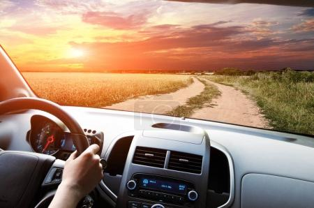 Car dashboard with drivers hand on the black steering wheel against blue sky with clouds