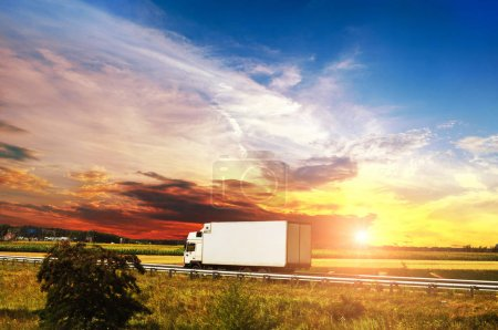 White box truck on the countryside road against night sky with beautiful sunset