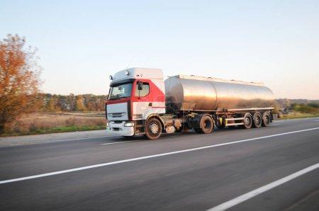 Foto de Grandes petroleros de combustible metálico transportan combustible en la carretera rural en movimiento con bosques contra cielo claro. - Imagen libre de derechos