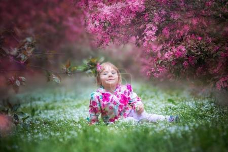 Little girl in blooming garden
