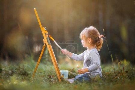 Photo for Little girl painting at easel in autumn park - Royalty Free Image