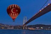 Red Hot Air balloons flying over Bosphorus Bridge at night. Ista