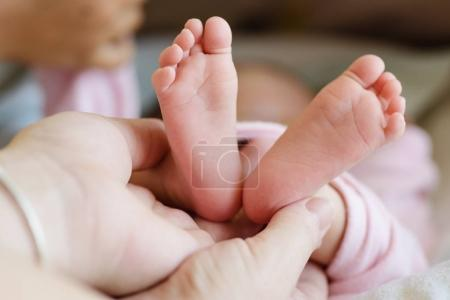 newborn's foot in mother hand
