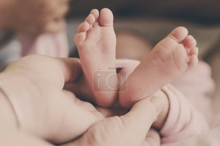 newborn's foot in the mother hand