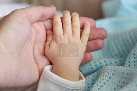 newborn's foot in mother hand