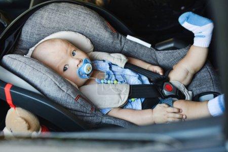 Photo pour Bébé garçon assis en voiture seat anf à la recherche dans la fenêtre - image libre de droit
