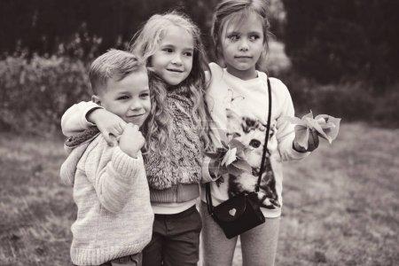 three kids having fun in autumn park