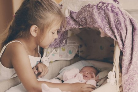 Photo for Little girl looking at the newborn baby in crib - Royalty Free Image