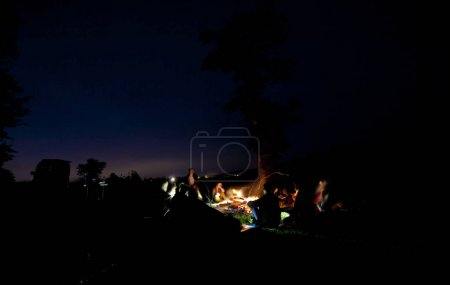 The company of young people are sitting around the bonfire and s