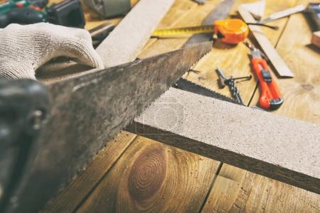 Man is sawing a wooden plank