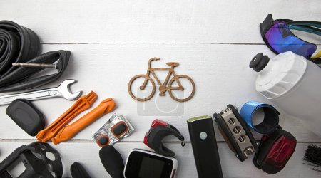 Photo pour Beaucoup de différents accessoires de vélo couché sur une table en bois autour d'une petite icône de vélo - image libre de droit