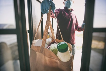 Photo for The delivery man gives the bag from grocery store to the woman to her home - Royalty Free Image