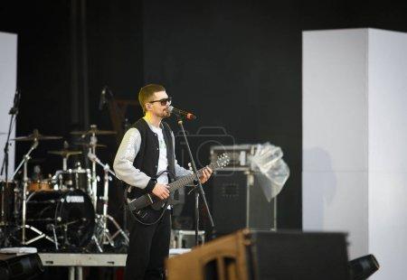 Photo pour Moscou - quejoue 14, 2017: Cool chanteur rap & rock Noize Mc se produire sur scène. Concert en gros plein air pour le public russe. Guy de joueur de guitare jeunes chanter sur scène & rap au rythme - image libre de droit