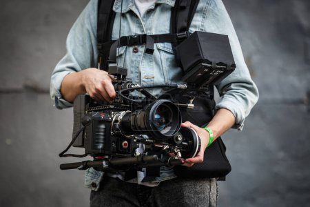 Photo for MOSCOW - 14 JUJY,2017: Professional video camera opertor guy film event with huge cam mounted on stabilized vest.Red One camera shoot high quality video footage in 5k resolution - Royalty Free Image