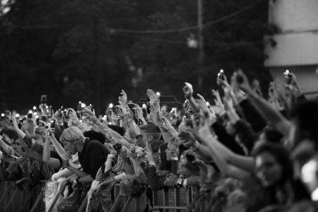 Photo pour Moscou - quejoue 14, 2017: Public grand concert jeunes mis mains jusqu'à la musique préférée. Foule de concert s'amuser à l'événement musical live du plein air l'été. Ligne de front à l'escrime securty - image libre de droit