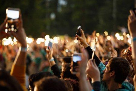 Photo pour Moscou - quejoue 14, 2017: Grande foule d'amateurs de musique film concert avec téléphone intelligent dans la main. Festival de musique se pressent tournage événement de divertissement de plein air avec les smartphones. Fond de bokeh - image libre de droit