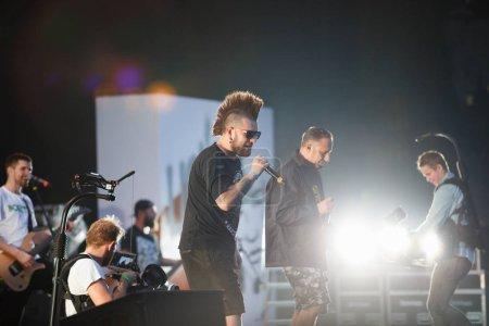 Photo pour Moscou - quejoue 14, 2017: Chanteur Cool punk rock avec coupe de cheveux iroquois chanter sur scène durant le grand concert de Noize mc. Interprète à la mode hard rock avec des tatouages chanter sur scène - image libre de droit