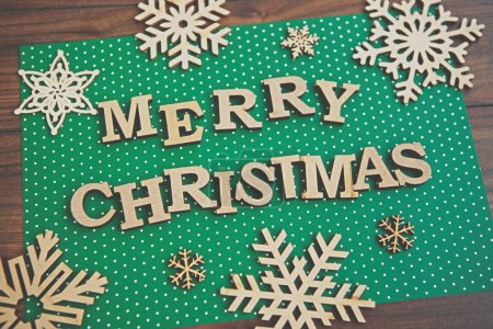 Photo for Merry Christmas background.Handmade wooden snowflakes and letters shot in flat lay style on green paper backdrop.Winter holiday home decor - Royalty Free Image