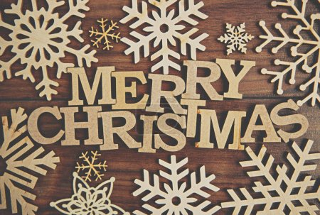 Photo for Vintage brown Merry Christmas background with rustic wooden letters and snowflakes shot in flat lay style from above.Winter holiday wallpaper with hand made crafts and home decor - Royalty Free Image