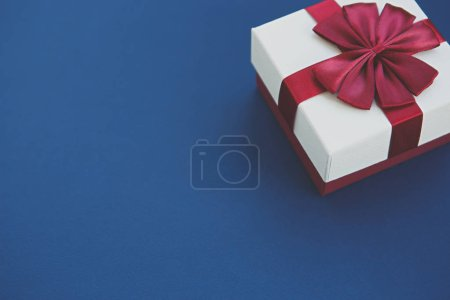 Photo for Gift box with red ribbon on blue background.Christmas & New Year present package in white and red colors decorated with bow.Beautiful minimalistic wallpaper with empty space for text - Royalty Free Image
