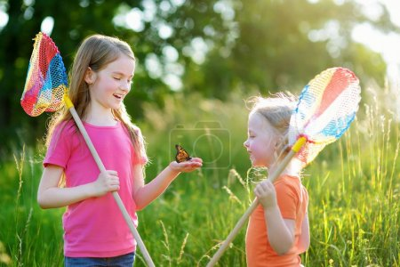 Two sisters catching butterflies