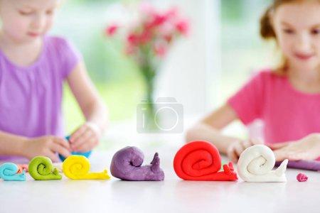 Photo pour Figures d'escargots et de petites filles avec glaise à modeler colorée à la garderie - image libre de droit