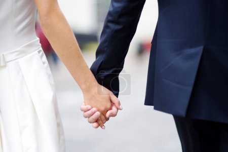 Bride and groom holding their hands on wedding day...