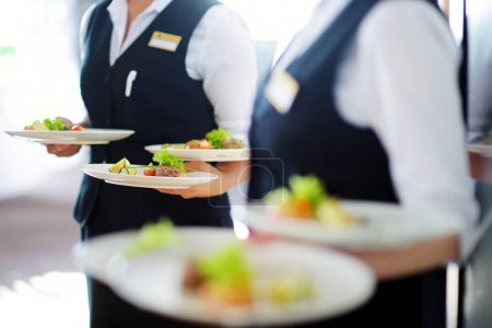 Waiters carrying plates with dishes