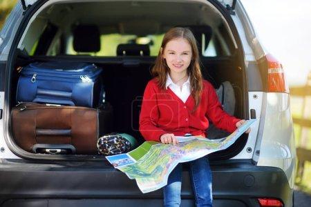Kid sitting in car, examining map.
