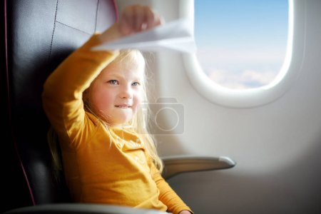Enfant jouant avec avion en papier