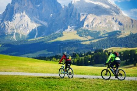 Tourists cycling on altitude Alpine meadow