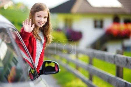 girl sticking head out car window