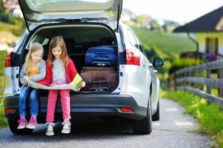 girls sitting in open trunk of car