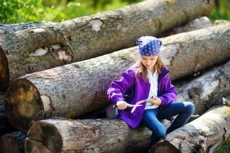 little girl sitting on tree logs