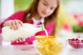 Pretty child purring milk in bowl