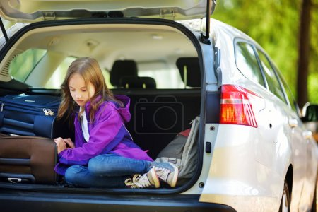 girl sitting near suitcases in trunk of car