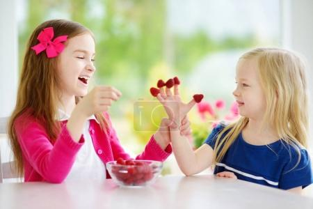 Two little girls eating raspberries