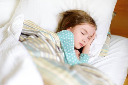 Adorable little girl sleeping in bed