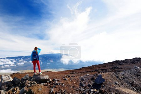 Photo for Tourist admiring breathtaking view of Mauna Loa volcano on the Big Island of Hawaii. The largest subaerial volcano in both mass and volume, Mauna Loa has been considered the largest volcano on Earth - Royalty Free Image